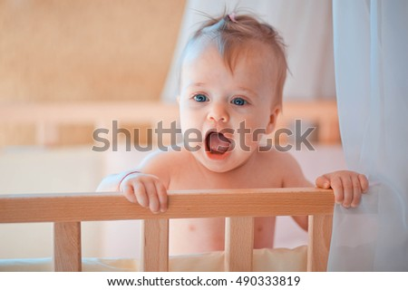 incredibly beautiful and cute little girl stands in crib
