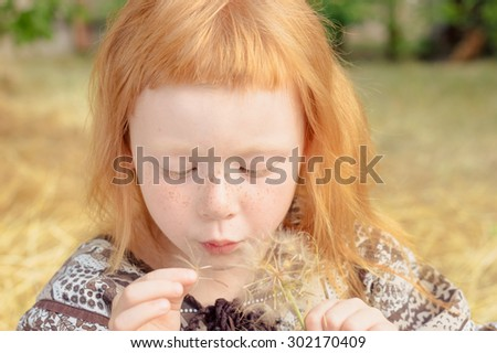 incredibly beautiful red-haired girl makes a wish and blows on a dandelion - stock photo