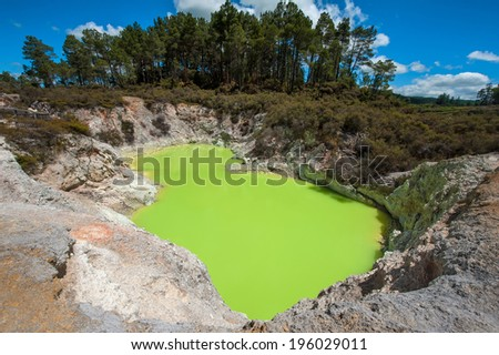 Incredibly green and highly toxic Devil's Bath crater lake at Wai-O-Tapu geothermal area, New Zealand - stock photo