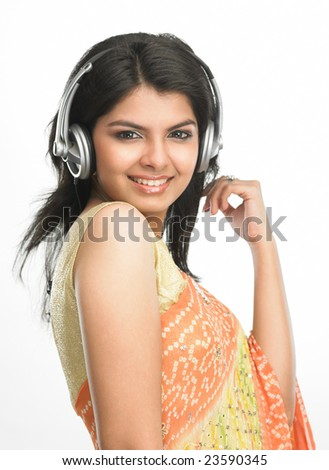 indain woman in sari with head phones - stock photo