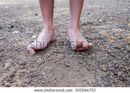 Indecision in childhood - kids feet on barren dry arid ground, Kid dirty feet on barren dry arid ground. Bare feet on ground