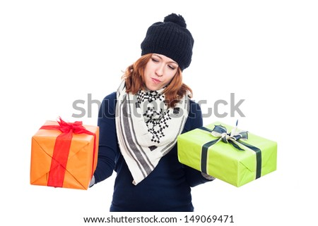 Indecisive winter woman holding two presents, isolated on white background. - stock photo