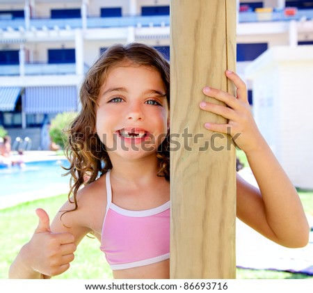indented kid girl ok gesture in pool garden holding sunroof pole - stock photo