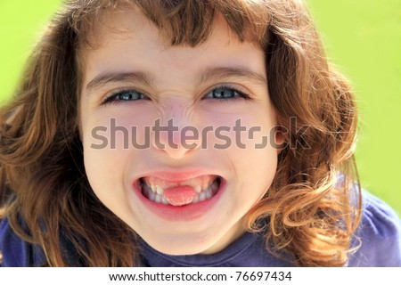 indented little girl sticking tongue between teeth smiling portrait - stock photo
