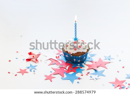 independence day, celebration, patriotism and holidays concept - close up of glazed cupcake or muffin with burning candle and stars cofetti decoration on table at 4th july party - stock photo