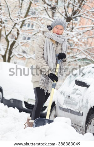Independent woman shoveling her parking lot after a winter snowstorm. - stock photo