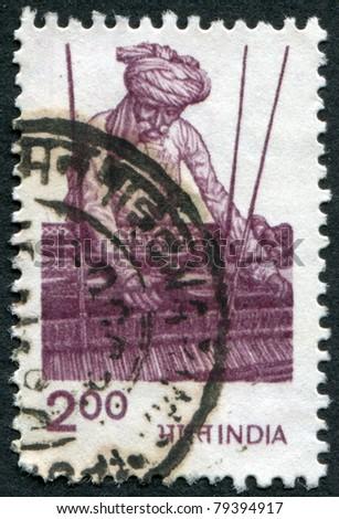 INDIA - CIRCA 1983: A stamp printed in India, shows a man for weaving, circa 1983 - stock photo