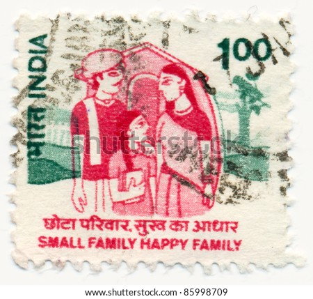"INDIA - CIRCA 1994: A stamp printed in India, shows Family of 3 in front of house with the inscription ""small family happy family"", circa 1994 - stock photo"