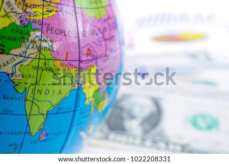 india close up globe world map on us dollar banknote money chart graph finance