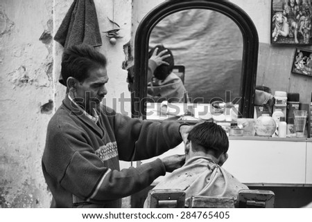 INDIA, Delhi; 21 january 2007, street barber at the Uttar Pradesh market - EDITORIAL - stock photo