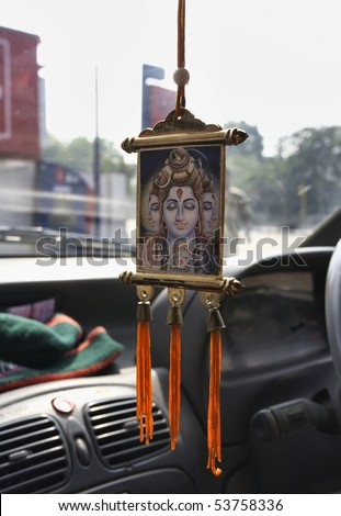 India, Delhi, Shiva sacred reproduction hanging off the ceiling of a taxi cab - stock photo