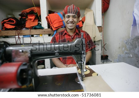 INDIA - FEB 26: Smiling textile worker in a small factory in Old Delhi on February 26, 2008 in Delhi, India. Many small factories provide the West with their clothes. - stock photo