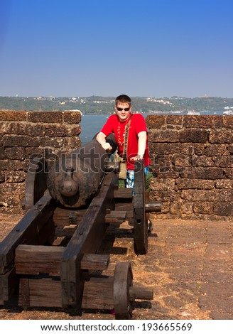 India. Goa. The teenager near a gun on a wall of an ancient fort - stock photo