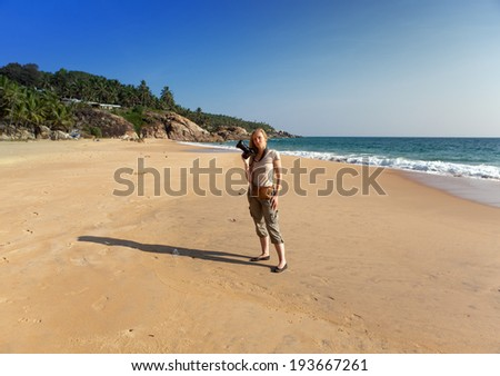 India. Kerala. The young beautiful woman with the camera on a beach.
