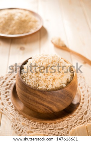 India organic basmati brown rice in wooden bowl on dining table. - stock photo