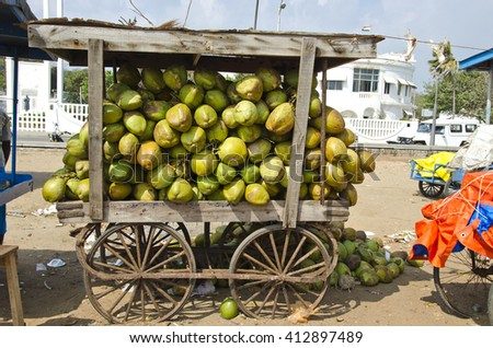 India, Puducherry, coconuts in mobile stall wagon on sale in the street on sunny day - stock photo