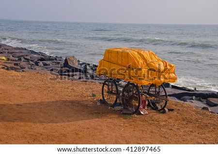 India, Puducherry, trolley with orange tied material by the sea - stock photo