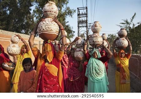 INDIA, Rajasthan, Jaipur; 24 january 2007, indian women taking food to a wedding - EDITORIAL - stock photo