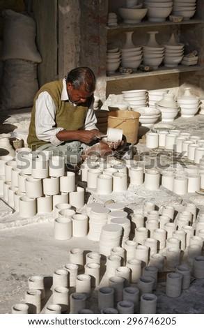 INDIA, Rajasthan, Jaipur; 25 january 2007, man working in a ceramics factory - EDITORIAL - stock photo