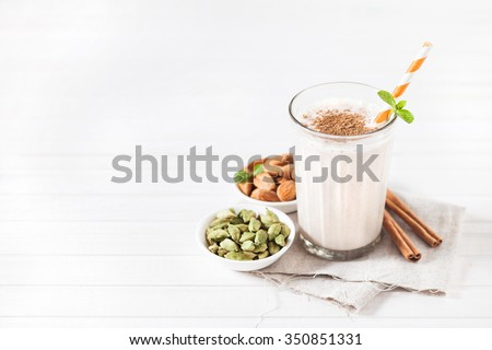 Indian almond lassi curd with spices cardamom and cinnamon in the glass with striped stick on white background with space for text