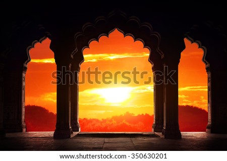 Indian arch silhouette in old temple at dramatic orange sunset sky background. Free space for text