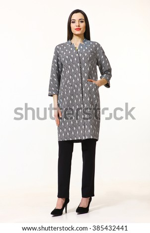indian asian eastern brunette business executive woman with straight hair style in black and white classical overcoat high heels shoes full length body portrait standing isolated on white - stock photo