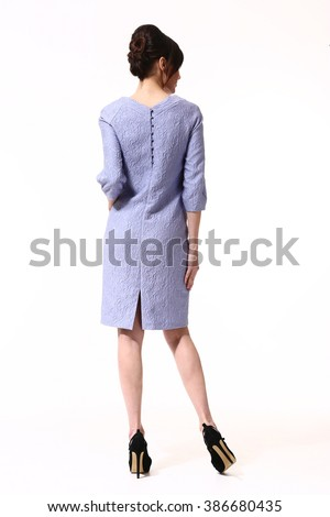 indian asian eastern brunette business executive woman with straight hair style in blue pastel formal dress high heel shoes standing full body length isolated on white back view - stock photo