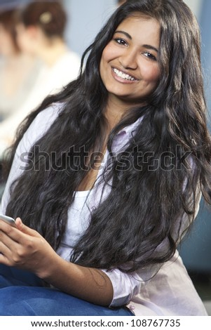 Indian Asian female student using tablet computer at college - stock photo