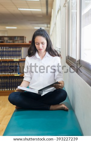 Indian, Asian girl student studying at the library, Reading,She sitting near the window