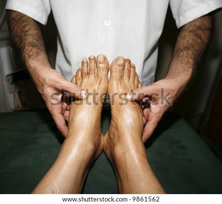 indian ayurvedic oil foot massage - stock photo