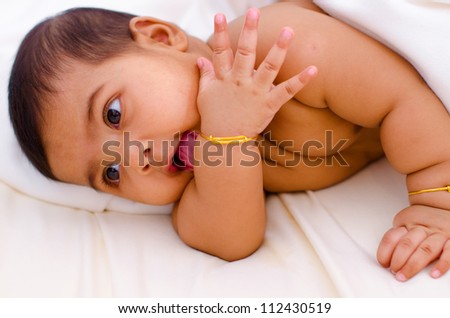 Indian baby girl licking her hand - stock photo