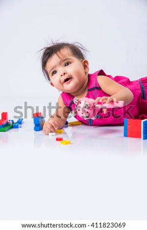indian baby playing with toys or blocks, asian infant playing with toys on white background, indian baby girl playing with toys, indian toddler playing with toys, indian baby girl lying on white floor - stock photo