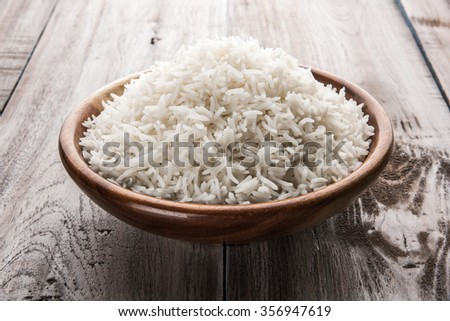 indian basmati rice, pakistani basmati rice, asian basmati rice, cooked basmati rice, cooked white rice, cooked plain rice in wooden bowl over brown wooden background - stock photo