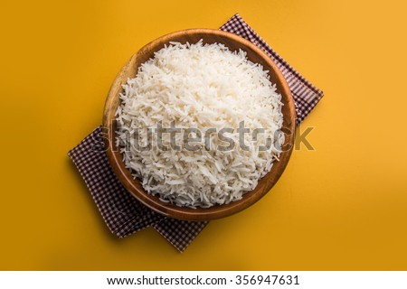 indian basmati rice, pakistani basmati rice, asian basmati rice, cooked basmati rice, cooked white rice, cooked plain rice in wooden bowl over yellow background - stock photo