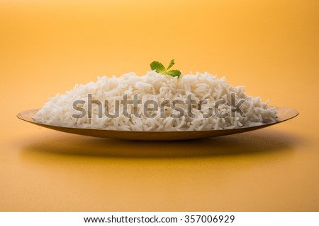indian basmati rice, pakistani basmati rice, asian basmati rice, cooked basmati rice, cooked white rice, cooked plain rice in oval brass bowl over yellow background - stock photo
