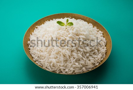 indian basmati rice, pakistani basmati rice, asian basmati rice, cooked basmati rice, cooked white rice, cooked plain rice in round brass bowl over green background - stock photo