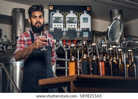 Indian bearded tattooed hipster male manufacturer tasting and presenting craft beer in the microbrewery.