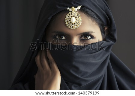 Indian beautiful Muslim girl portrait showing her eyes only. - stock photo
