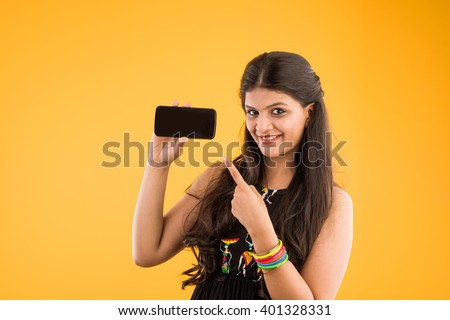 indian beautiful young girl with smartphone, beautiful girl holding smartphone over yellow background, asian girl with smartphone - stock photo