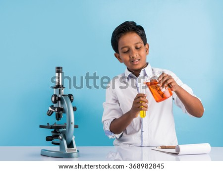 indian boy and chemistry experiment and microscope, asian boy with microscope and doing chemistry experiment, indian boy and science experiment - stock photo