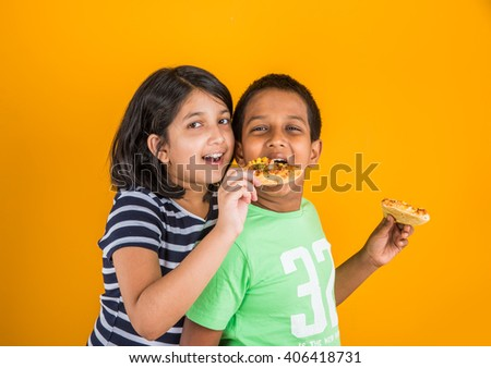 indian boy and girl eating pizza, asian kids eating pizza - stock photo