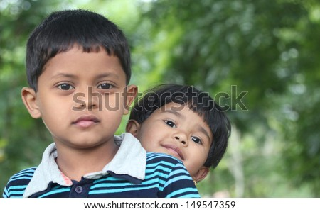 Indian boy & girl ( brother and sister ) playing & enjoying in a park. This summer time photo is of two beautiful kids sitting together in a garden which is seen in the background - stock photo