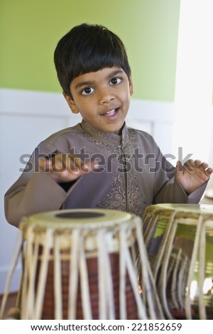 Indian boy playing drums - stock photo