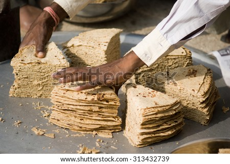 Indian bread Chapati cutting for group lunch in rural village Salunkwadi, Ambajogai, Beed, Maharashtra, India, South East Asia. - stock photo