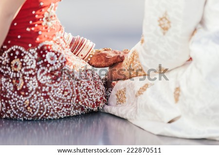 Indian bride and groom holding hands after the wedding ceremony - stock photo