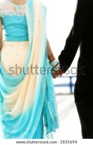 indian bride and groom walking away together - stock photo