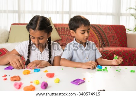 Indian brother and sister playing with playdough at home - stock photo