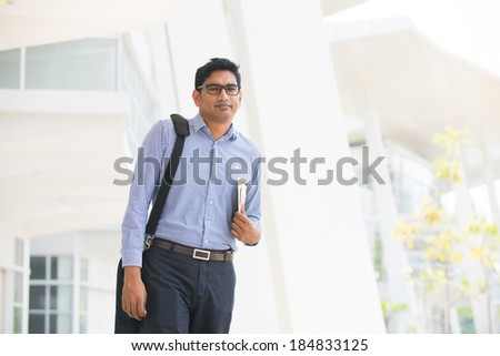 indian business male reading paper and walking  - stock photo