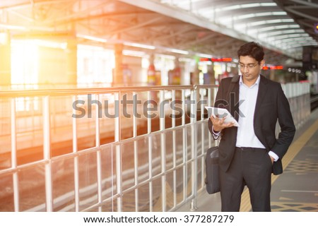 indian business male using tablet computer while waiting for train