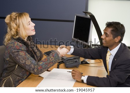Indian Business Man and Caucasian Woman Handshaking on a Deal - stock photo